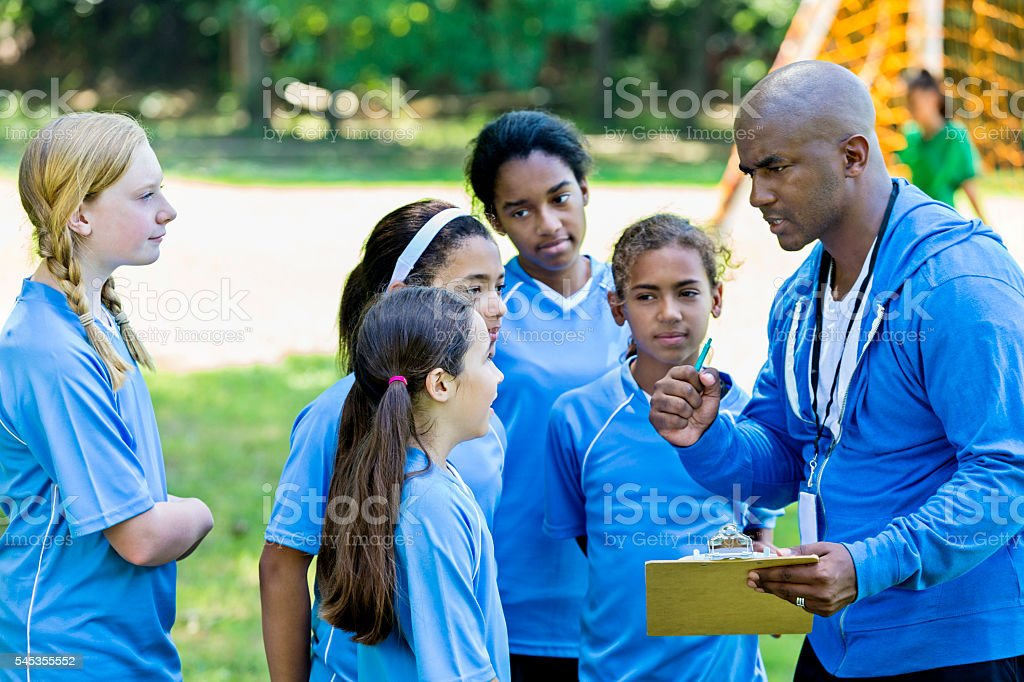 African American Soccer Coach giving pep talk to his team stock photo
