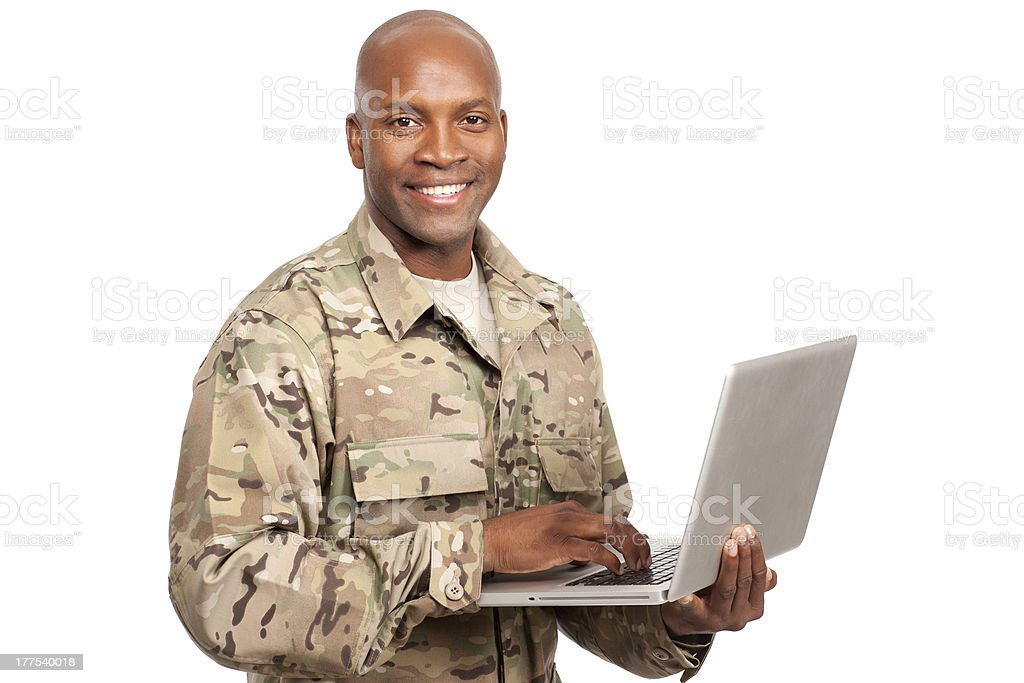 African American soldier smiles while typing on a computer stock photo