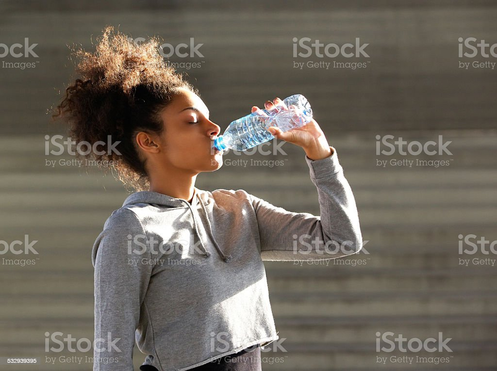 African american sports woman drinking from water bottle stock photo