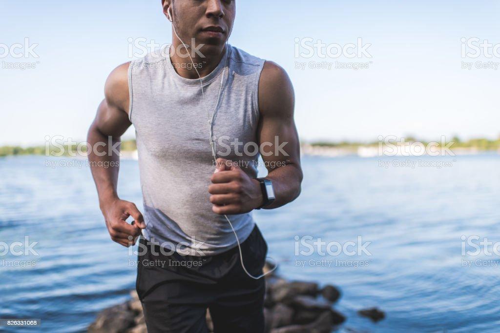 african american sportsman running at riverside stock photo