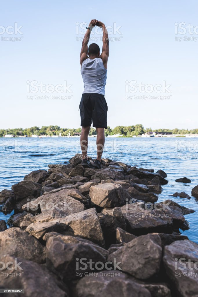 african american sportsman stretching at riverside stock photo