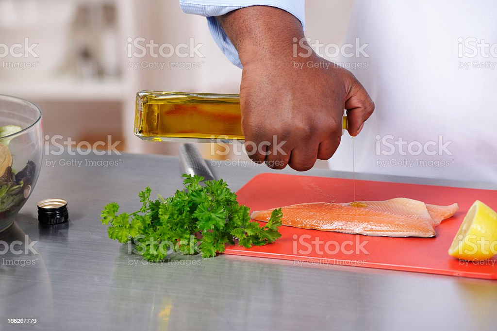 African American Sprinkling Olive Oil On Fish royalty-free stock photo