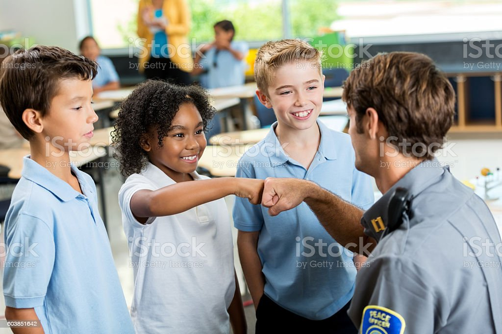 African American student gives policeman a fist bump at school stock photo