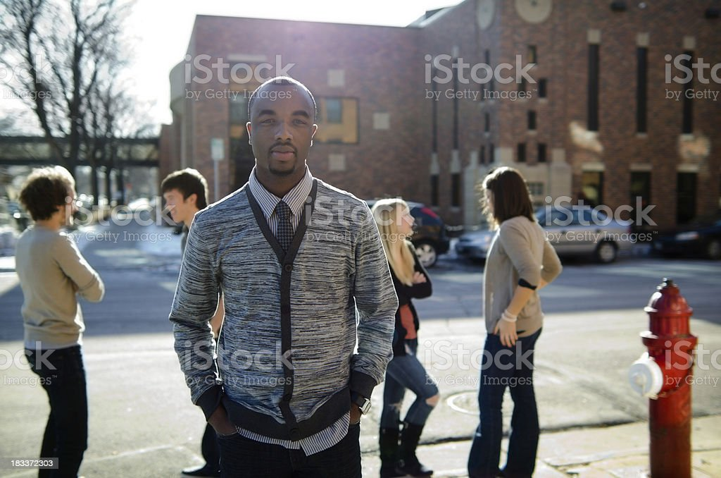 African American student standing with friends outside a college royalty-free stock photo