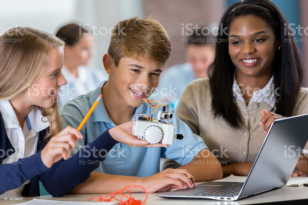 African American technology teacher helps students with robotics project stock photo