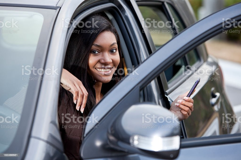 African American teen girl in parked car with mobile phone stock photo