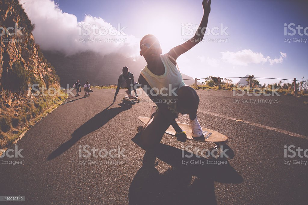 African American teen girl on a longboard doing downhill racing stock photo