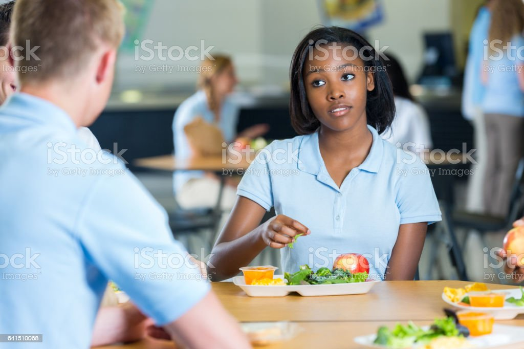African American teenage girl eats lunch with friends in school cafeteria stock photo