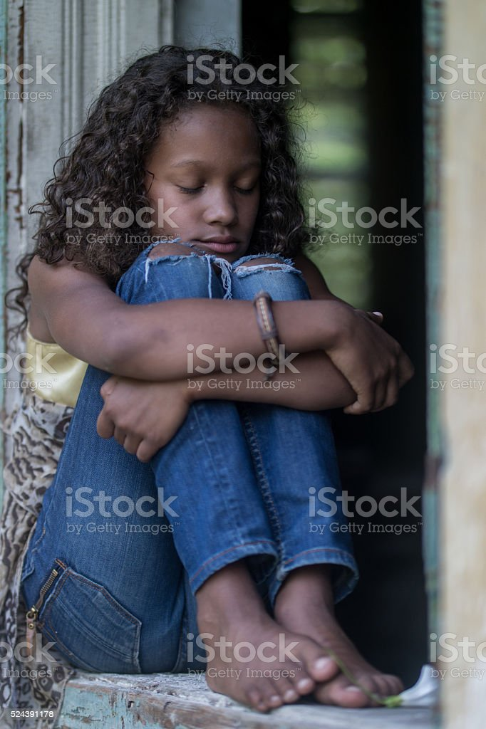 African American teenage girl hugging her knees with closed eyes stock photo
