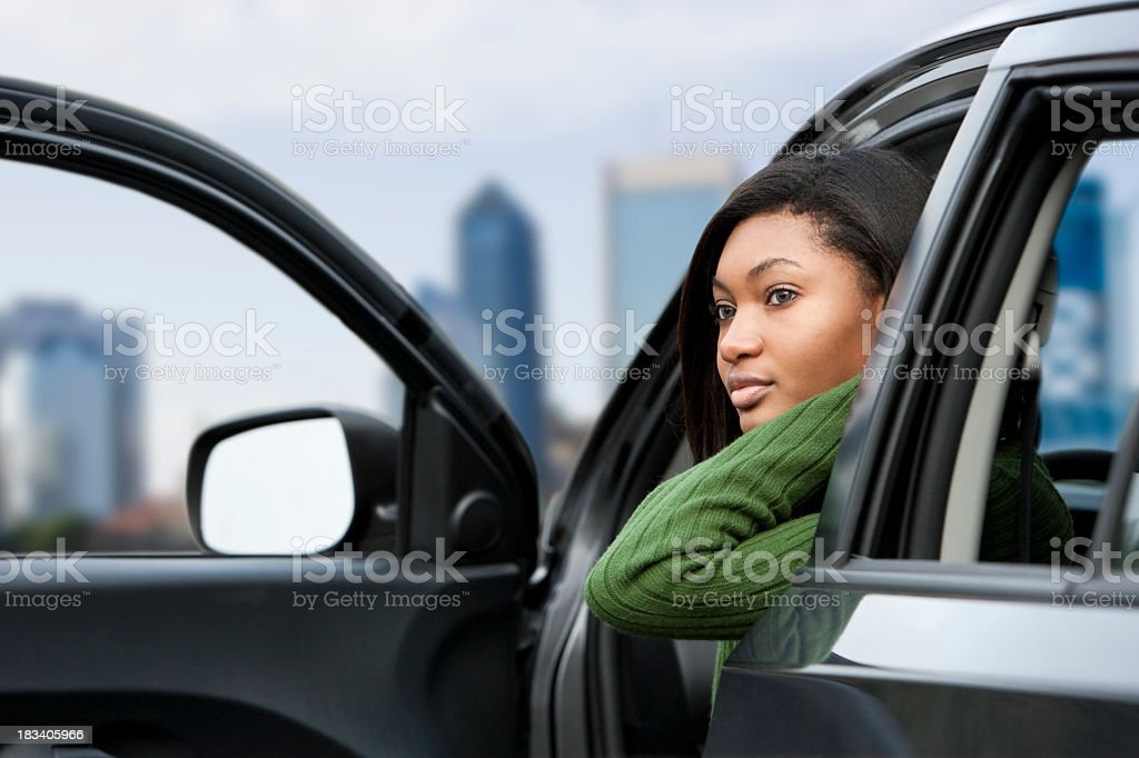 African American teenage girl in driver's seat of parked car stock photo