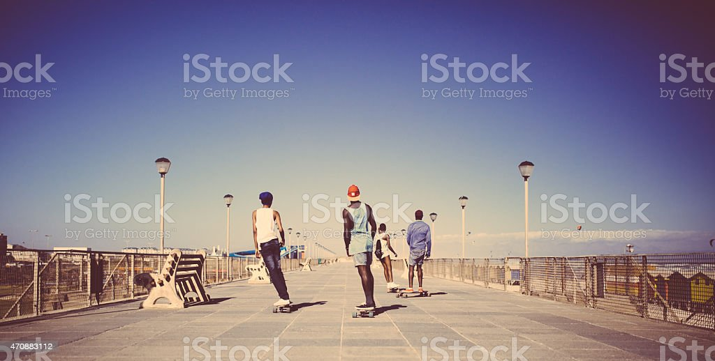 African American teenagers longboarding on a walkway at the beach stock photo