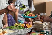 African American volunteer serves healthy meal in soup kitchen