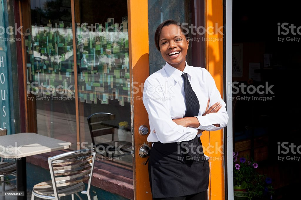 African American waitress standing outside restaurant stock photo