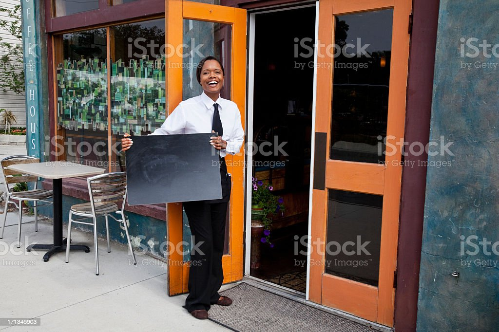 African American waitress standing outside restaurant with blank stock photo