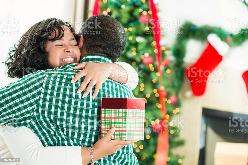 African American wife hugs husband after receiving Christmas gift stock photo