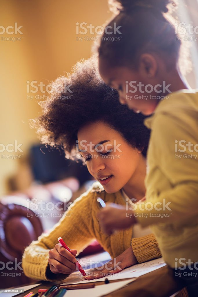 African American woman assisting her daughter in coloring. stock photo