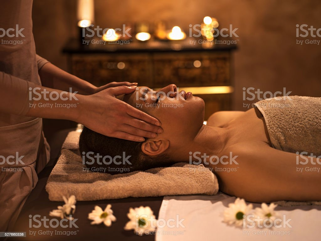 African American woman at the spa during facial massage. stock photo