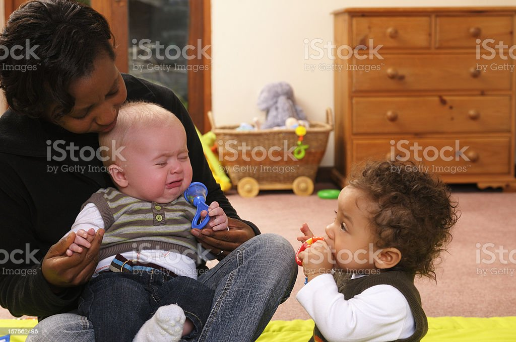 African American Woman Comforts An Unhappy Baby royalty-free stock photo