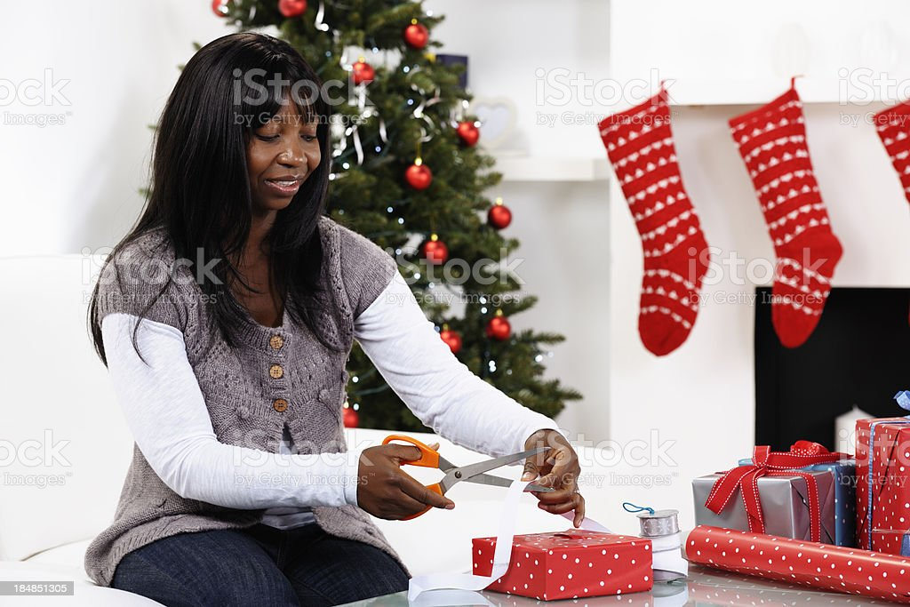 African American Woman Cutting Ribbon While Decorating Christmas Presents stock photo