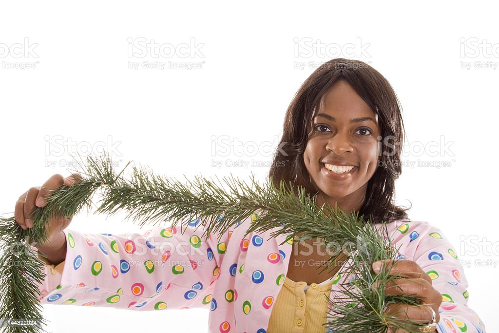 African American Woman Decorating for Christmas With Garland, Isolated Background royalty-free stock photo