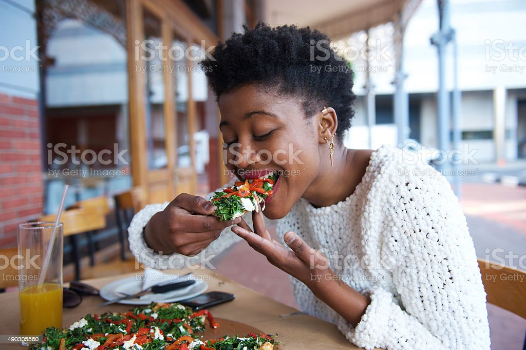 African american woman eating pizza at outdoor restaurant stock photo