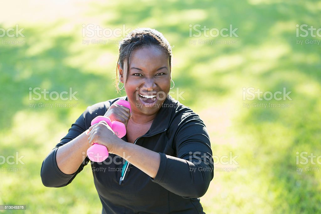 African American woman exercising with dumbbells stock photo