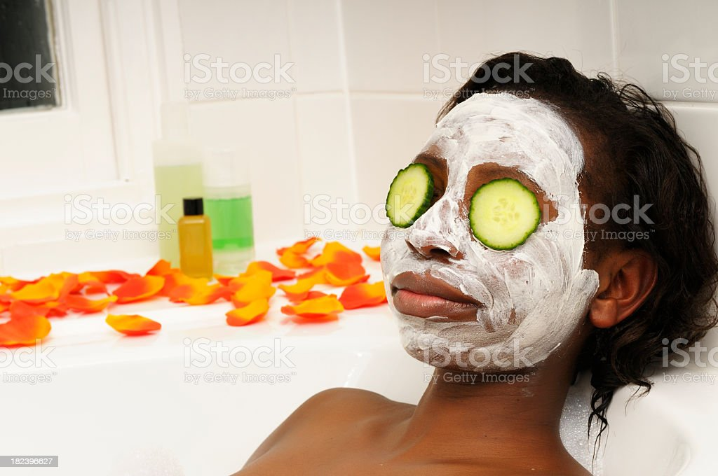African American Woman Having Facial with cucumber in the Bath royalty-free stock photo