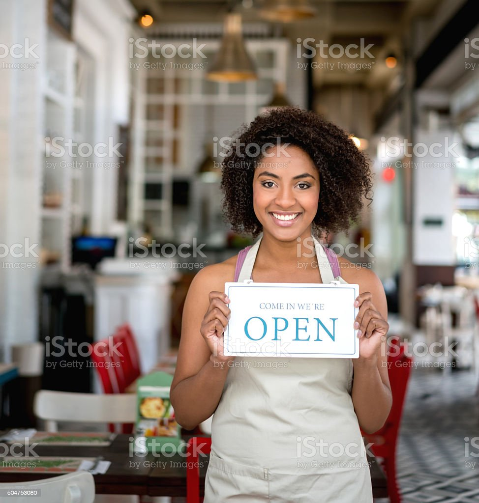 African American woman holding an open sign at a restaurant stock photo