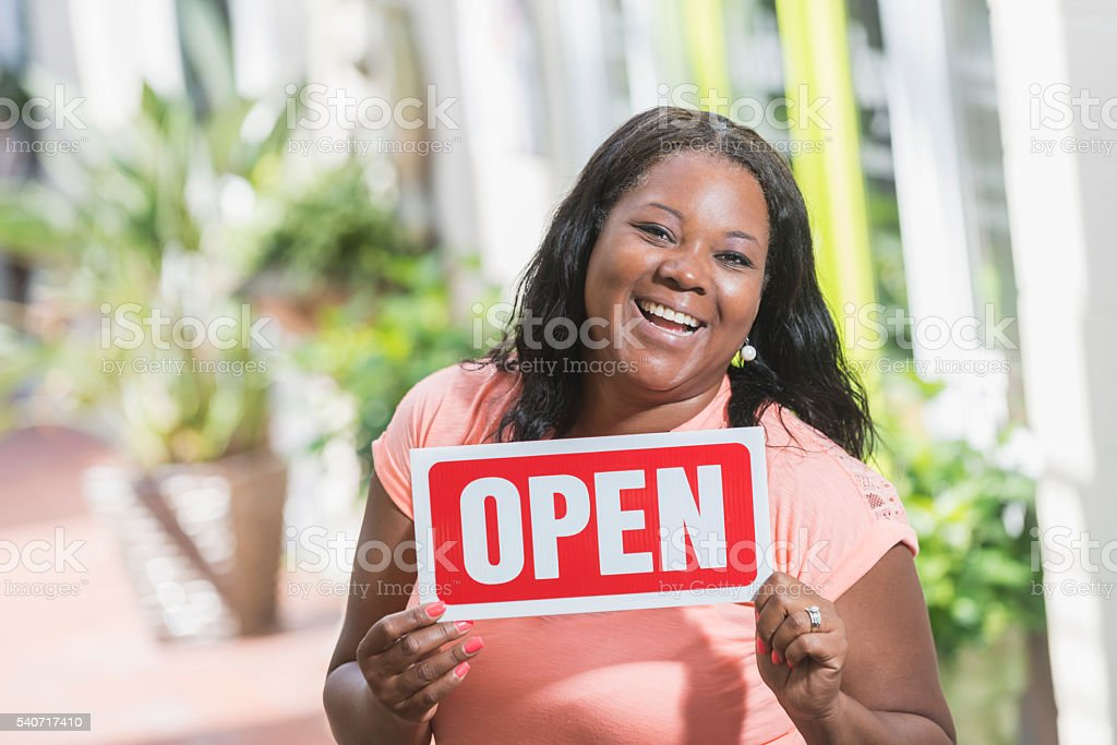 African American woman holding OPEN sign stock photo