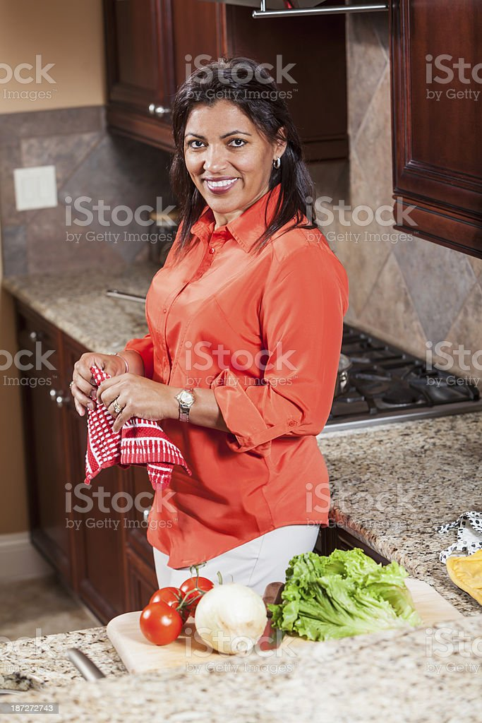African American woman in kitchen wiping hands on dishtowel stock photo