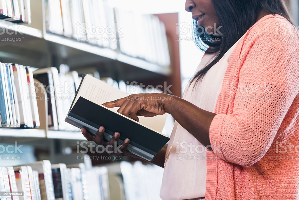 African American woman in library reading a book stock photo