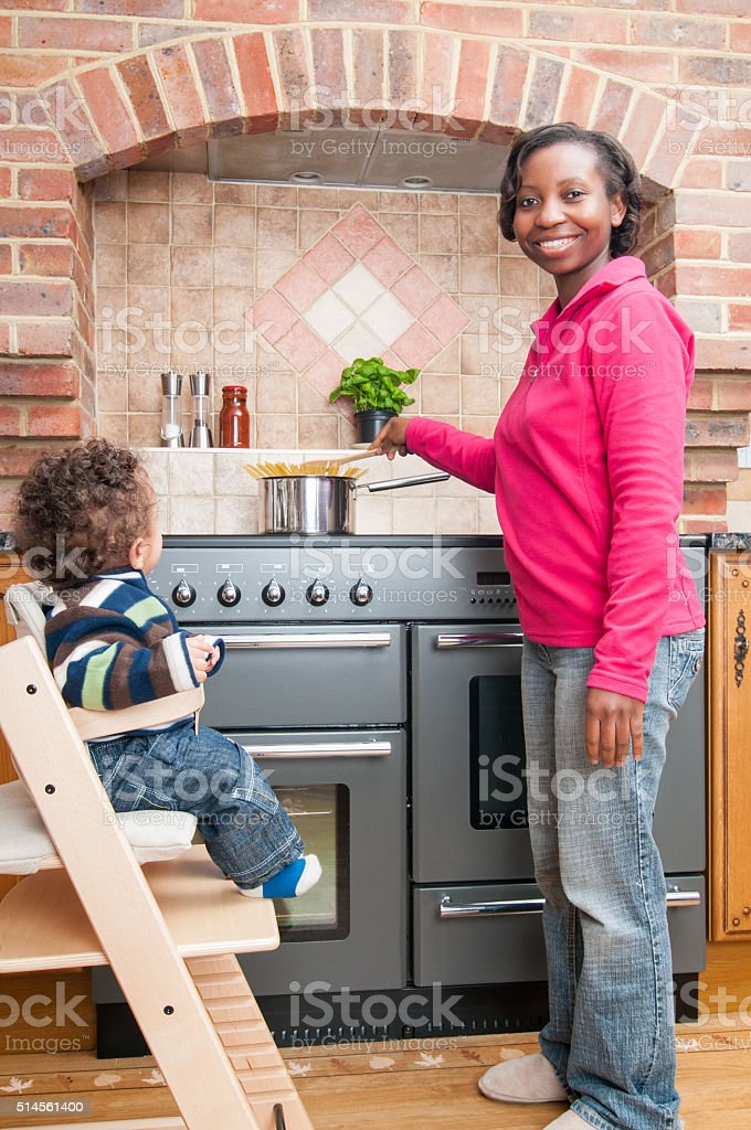 African American Woman Interacting With Son While Making Pasta stock photo