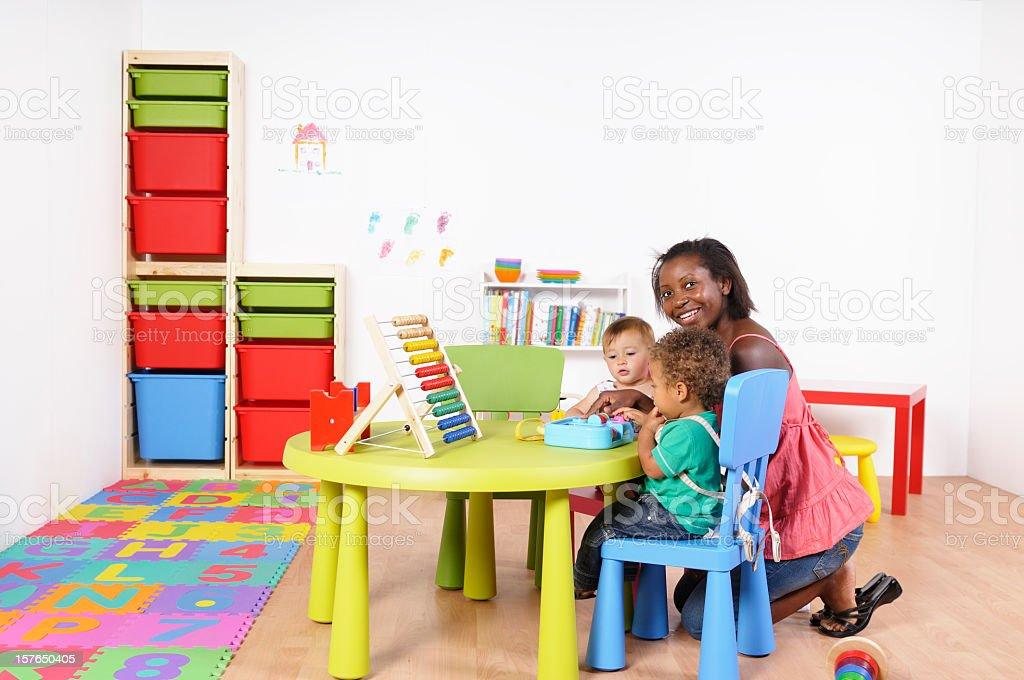 African American Woman Kneeling While Interacting With Babies stock photo