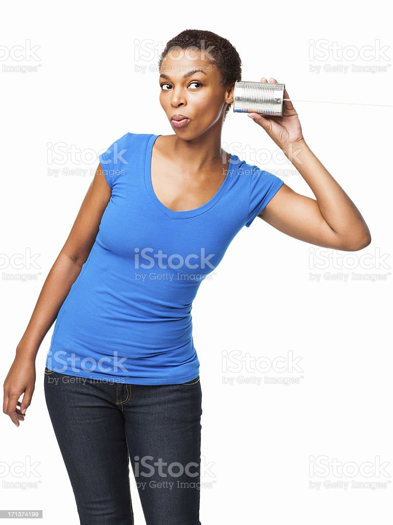 African American Woman Listening Through Tin Can Phone - Isolated royalty-free stock photo