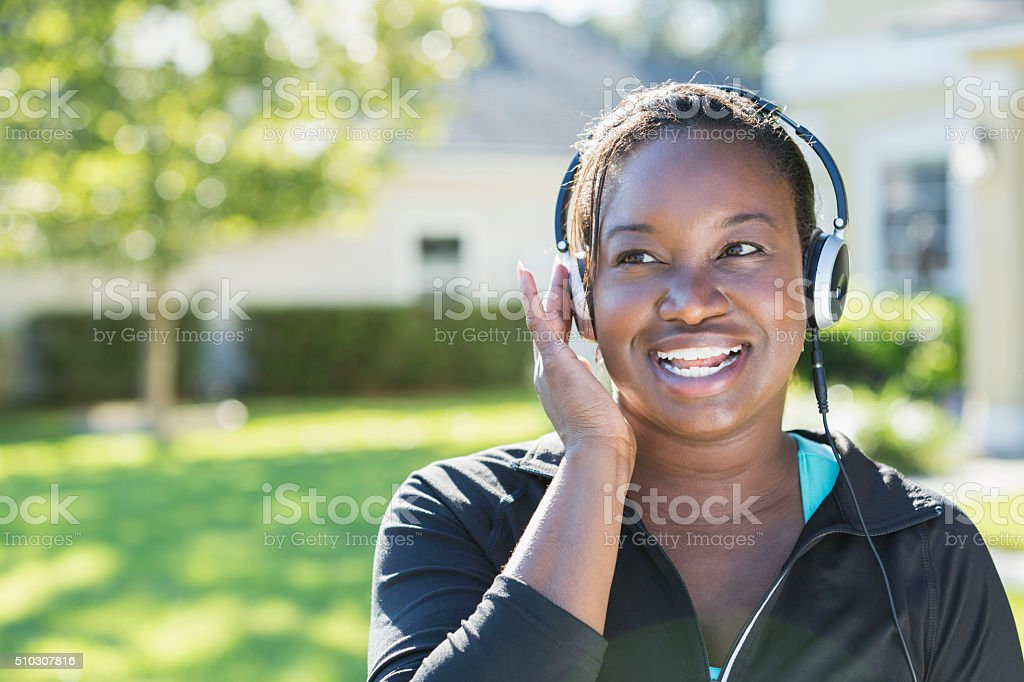 African American woman listening to music on headphones stock photo