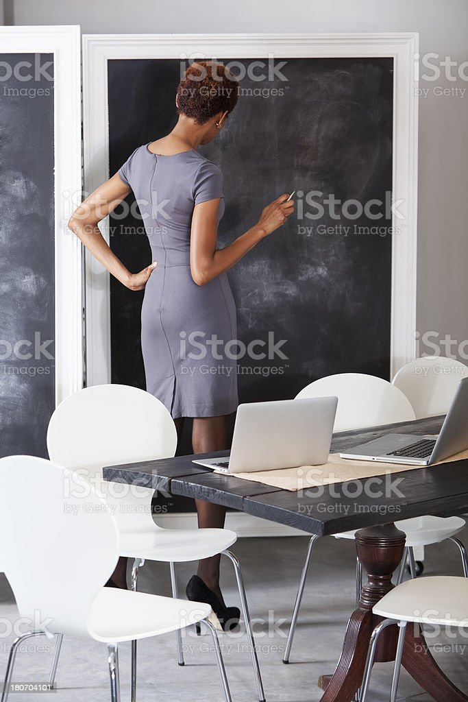 African American woman looking at blackboard stock photo