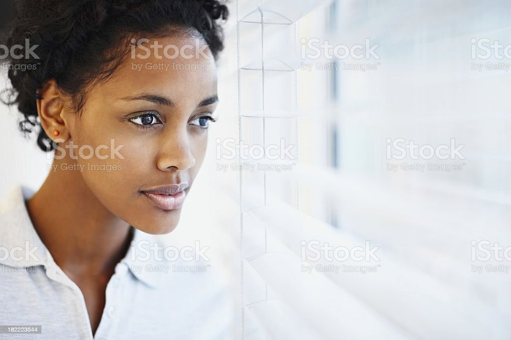 African American woman looking through blinds royalty-free stock photo