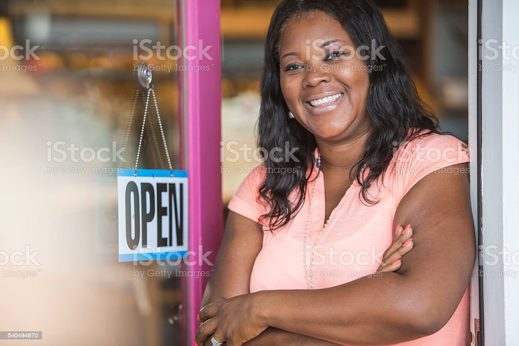 African American woman, OPEN sign on store door stock photo