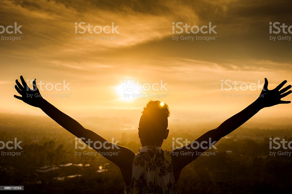 African American Woman Raising Arms at Sunset stock photo