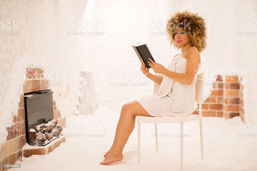 African American woman reading a book in salt room. stock photo