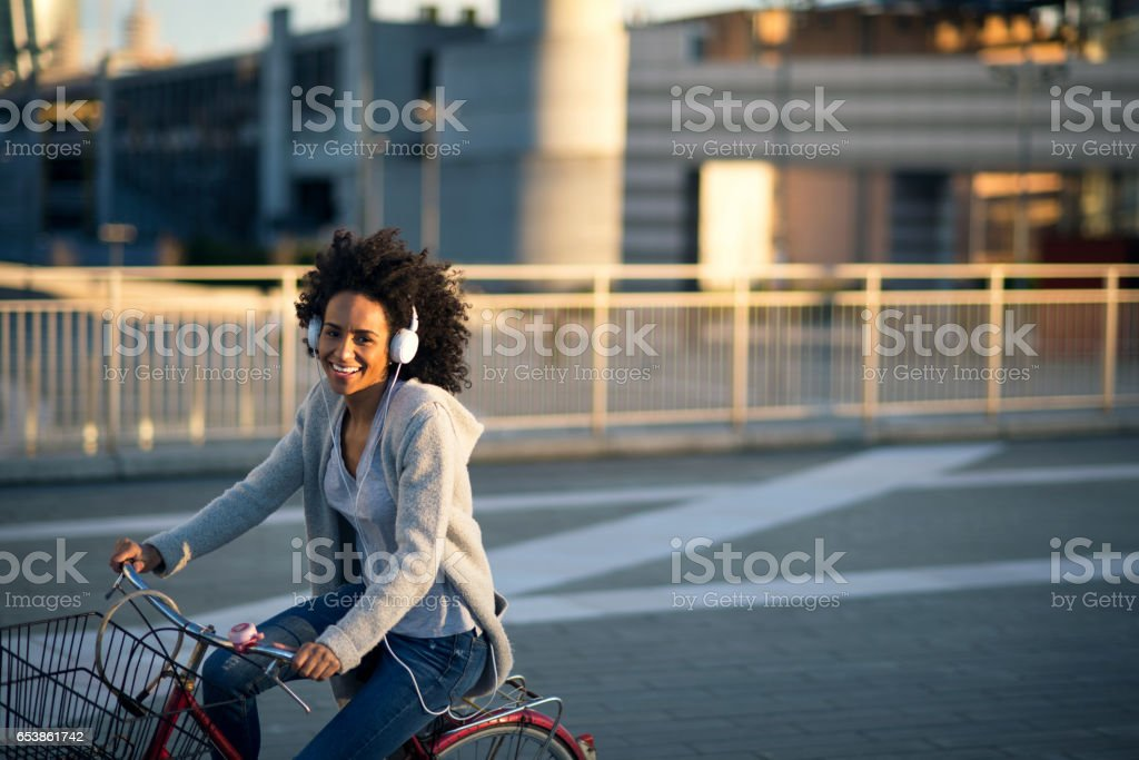 African American woman riding bike stock photo