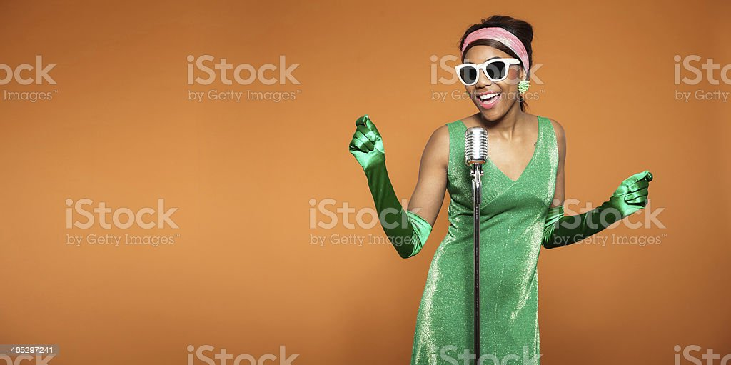 African American woman singing in a green dress and gloves  stock photo