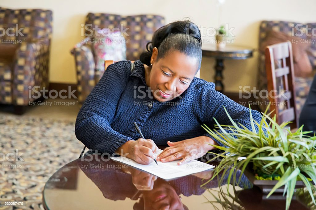 African American woman sitting at table completing job application stock photo