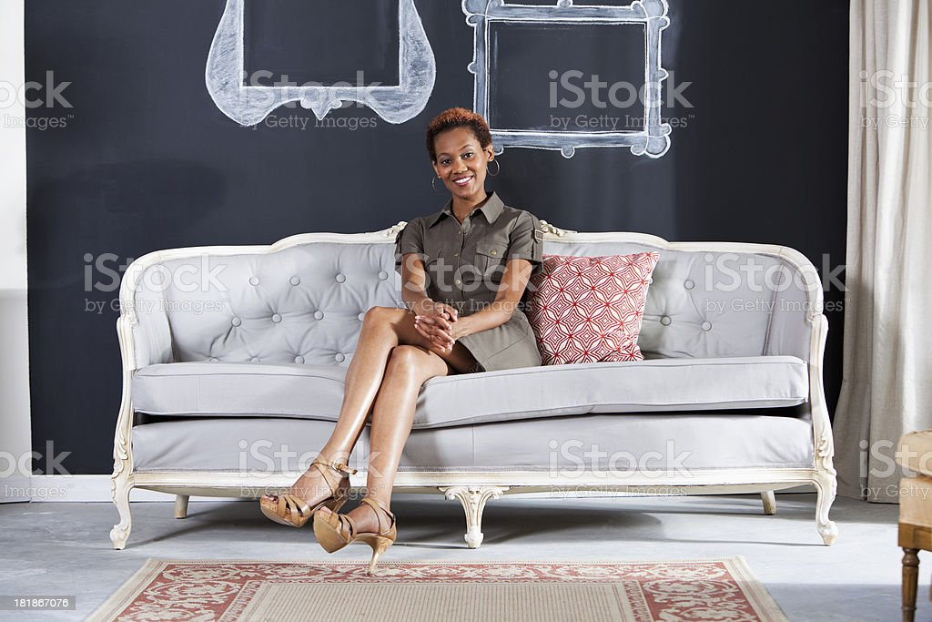 African American woman sitting on sofa stock photo