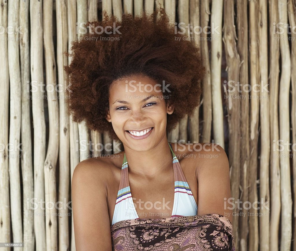 African American woman smiling against a bamboo wall royalty-free stock photo