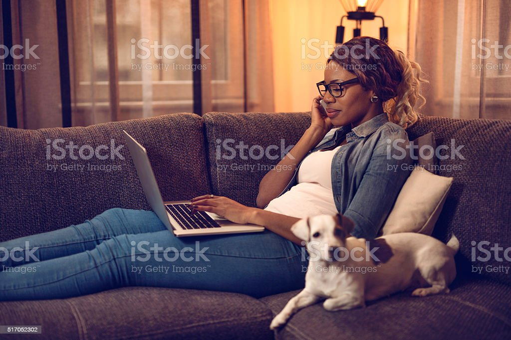African American woman talking on mobile phone and using laptop. stock photo