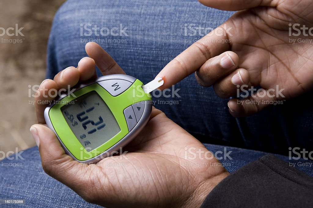 African American Woman Tests Blood Sugar stock photo