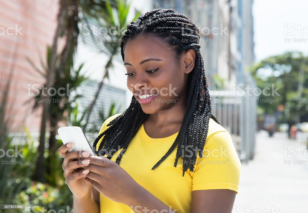 African american woman texting message with mobile phone stock photo