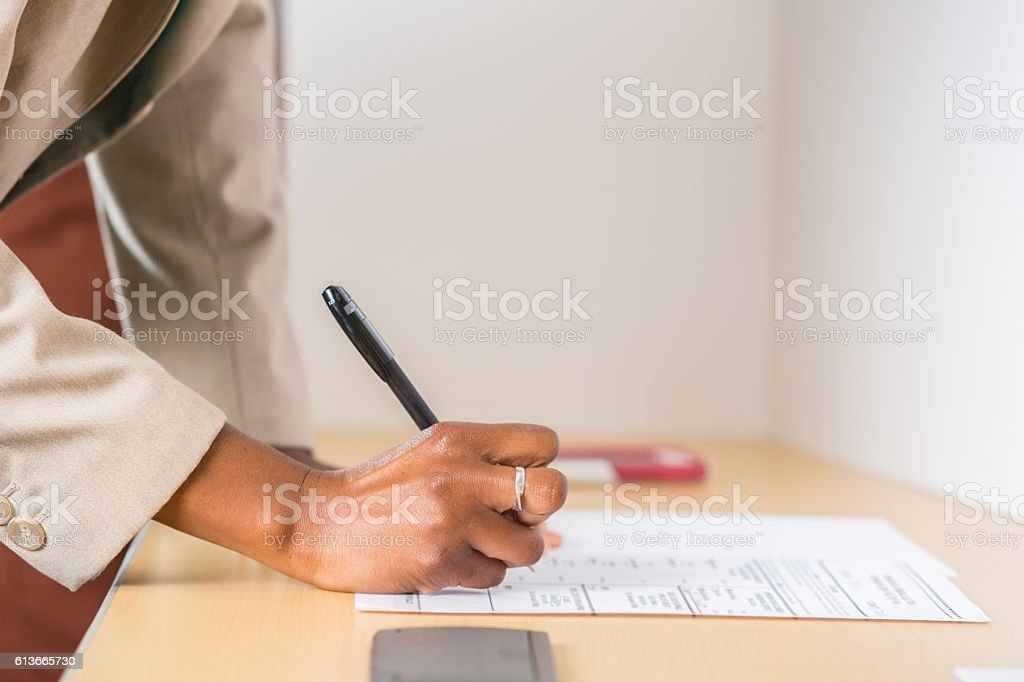 African American woman votes during election stock photo