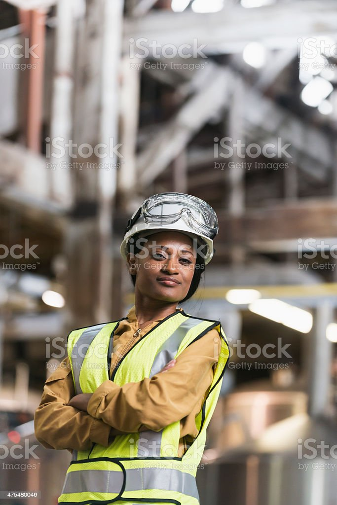 African American woman wearing hardhat and safety vest stock photo